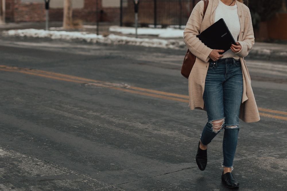 woman in beige coat and distressed blue jeans walking on road