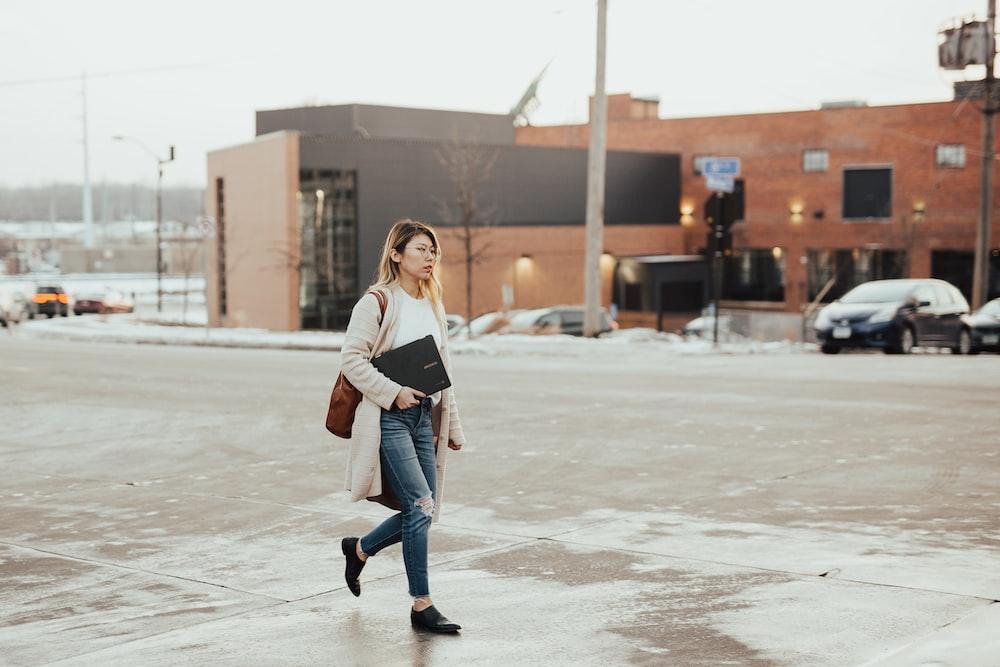 woman wearing beige cardigan carrying laptop while walking during daytime