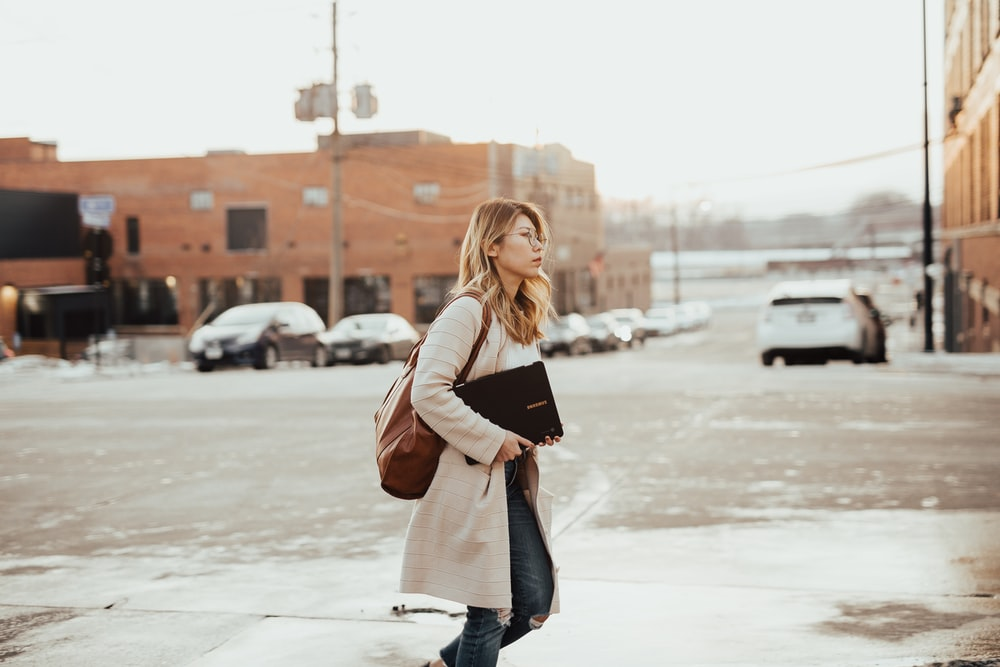 woman crossing street during daytime