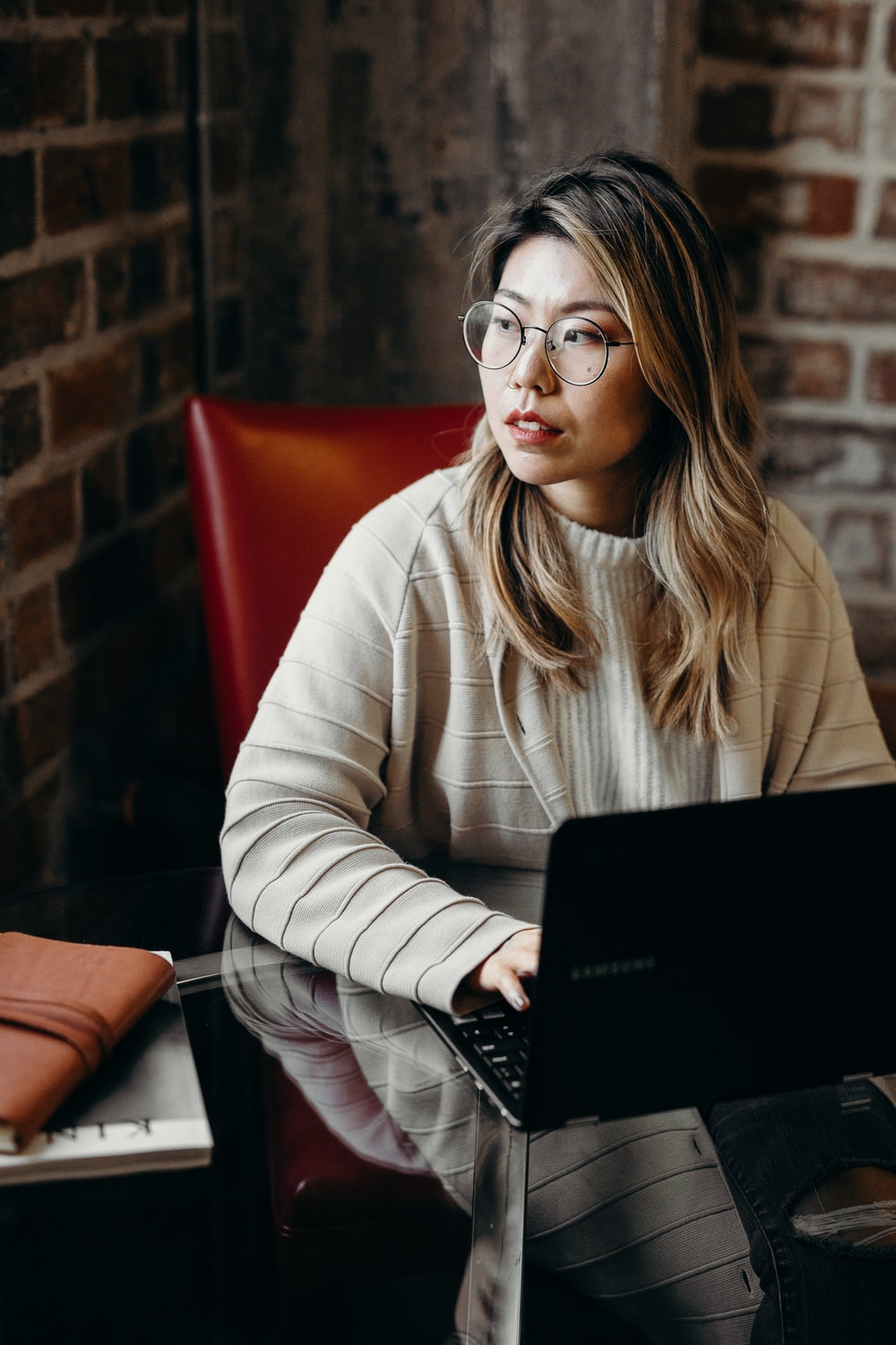woman looking sideways while holding black laptop computer