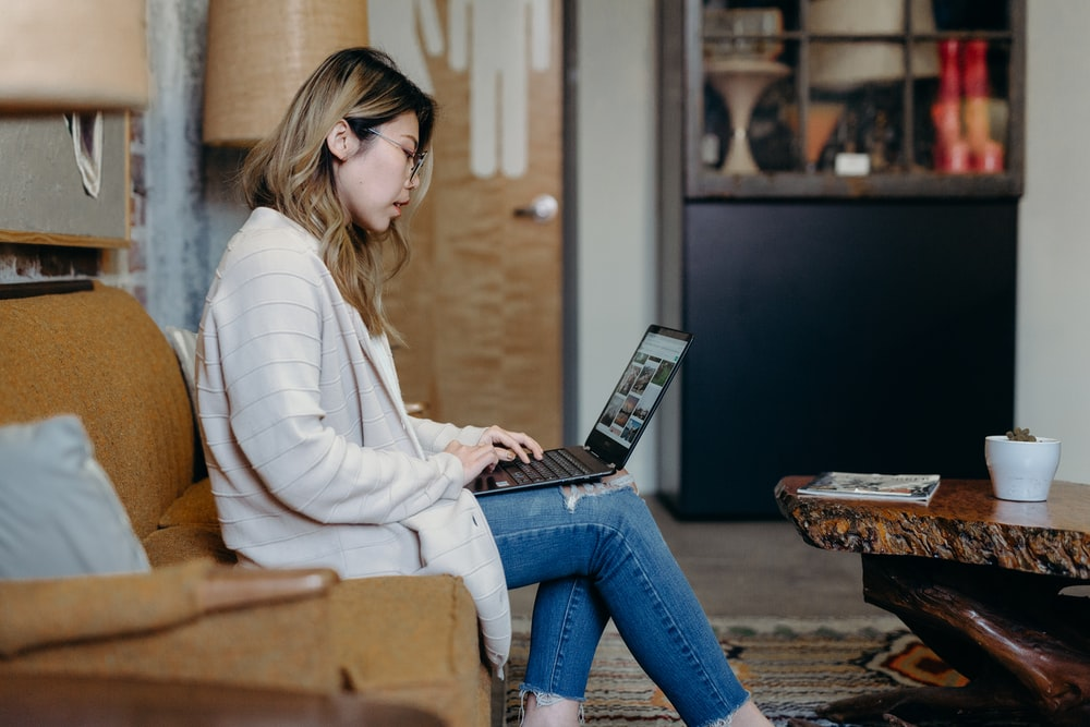 woman using laptop while sitting on sofa chair