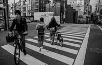 grayscale photo of three person on pedestrian lane