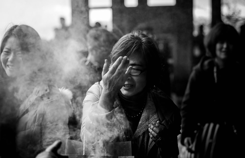 grayscale photography of woman covering her face from smoke