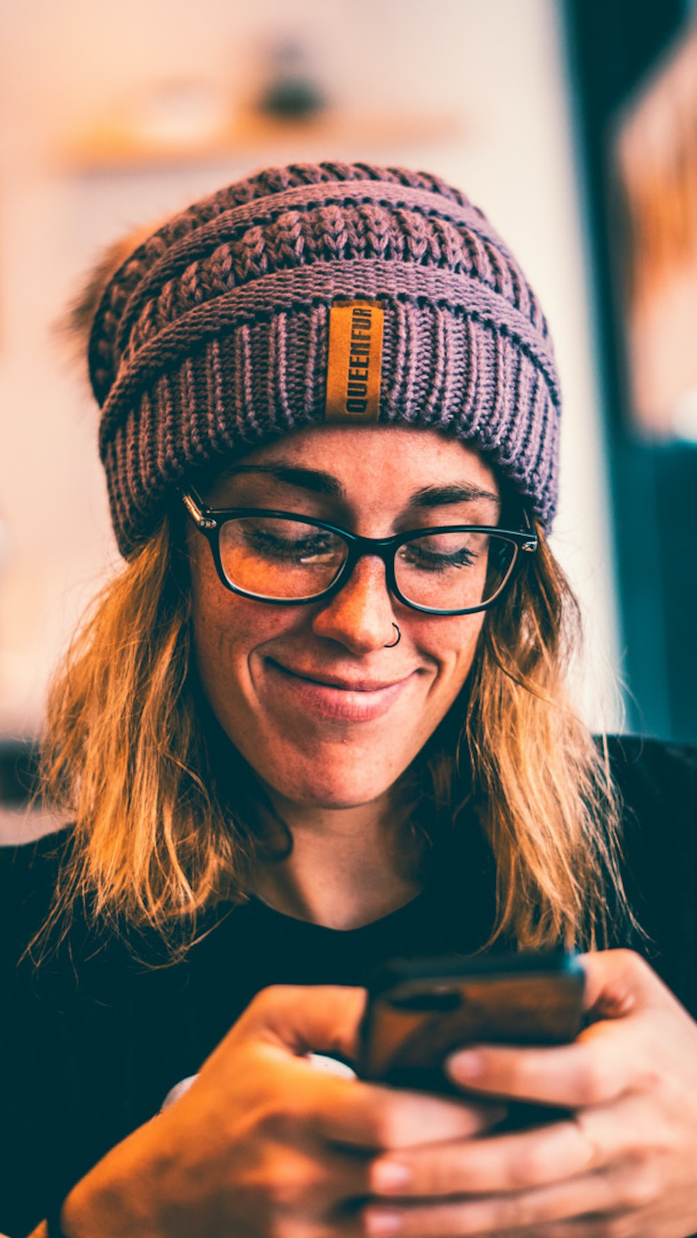 woman wearing black framed eyeglasses and grey knit beanie while using smartphone