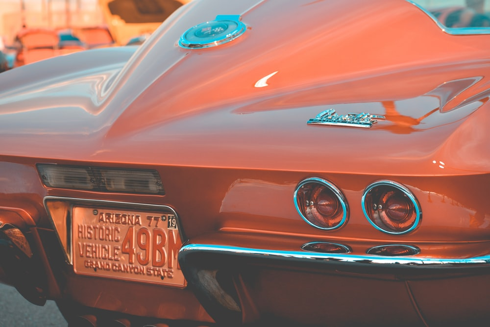 orange sports car rear view on park during daytime