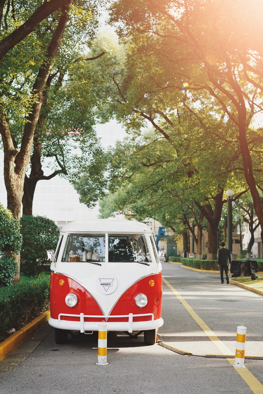vintage white and red vehicle parked on road beside tree