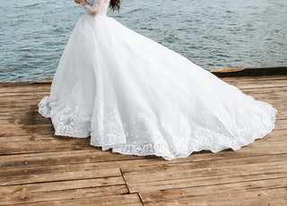 woman holding bouquet of flowers wearing wedding dress standing on dock during day