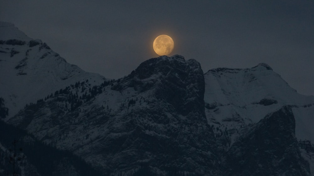 full moon over a snowy mountain top