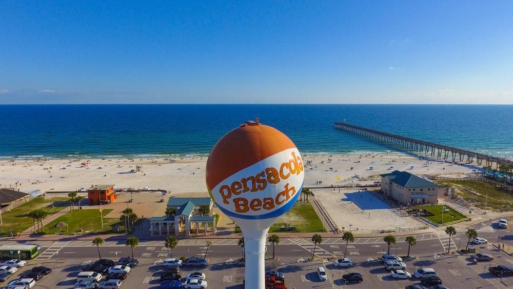 parking lot by the building near beach with orange and blue pensicola beach pole
