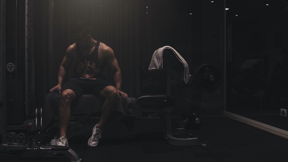 man wearing black tank top sitting on the weight bench