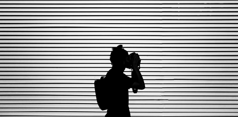 silhouette photography of person wearing bag
