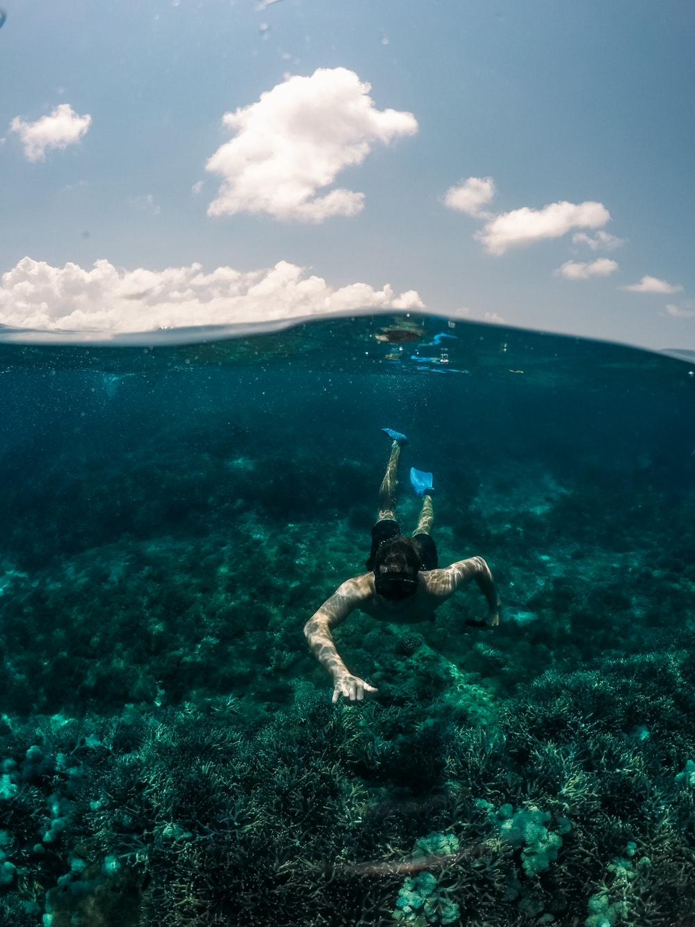 man swimming under clear blue sky
