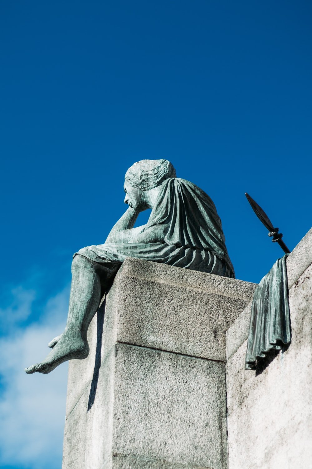 statue of man sitting on building