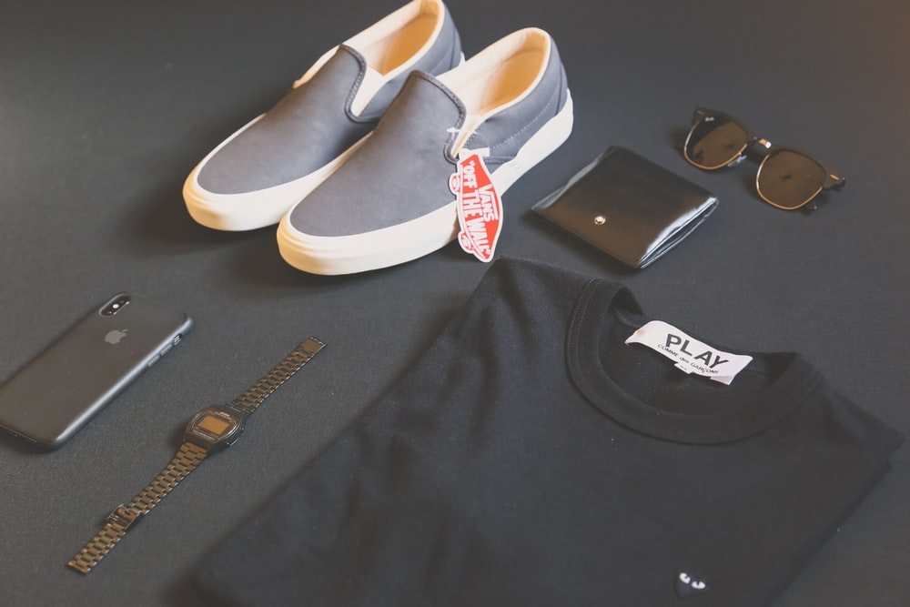 folded black Play shirt beside iPhone X, digital watch, and sneakers