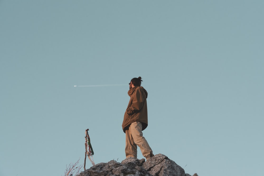 man in brown jacket standing on rock hill