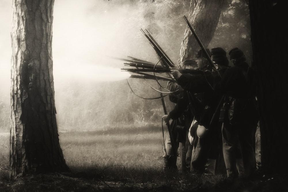 people using rifles near trees