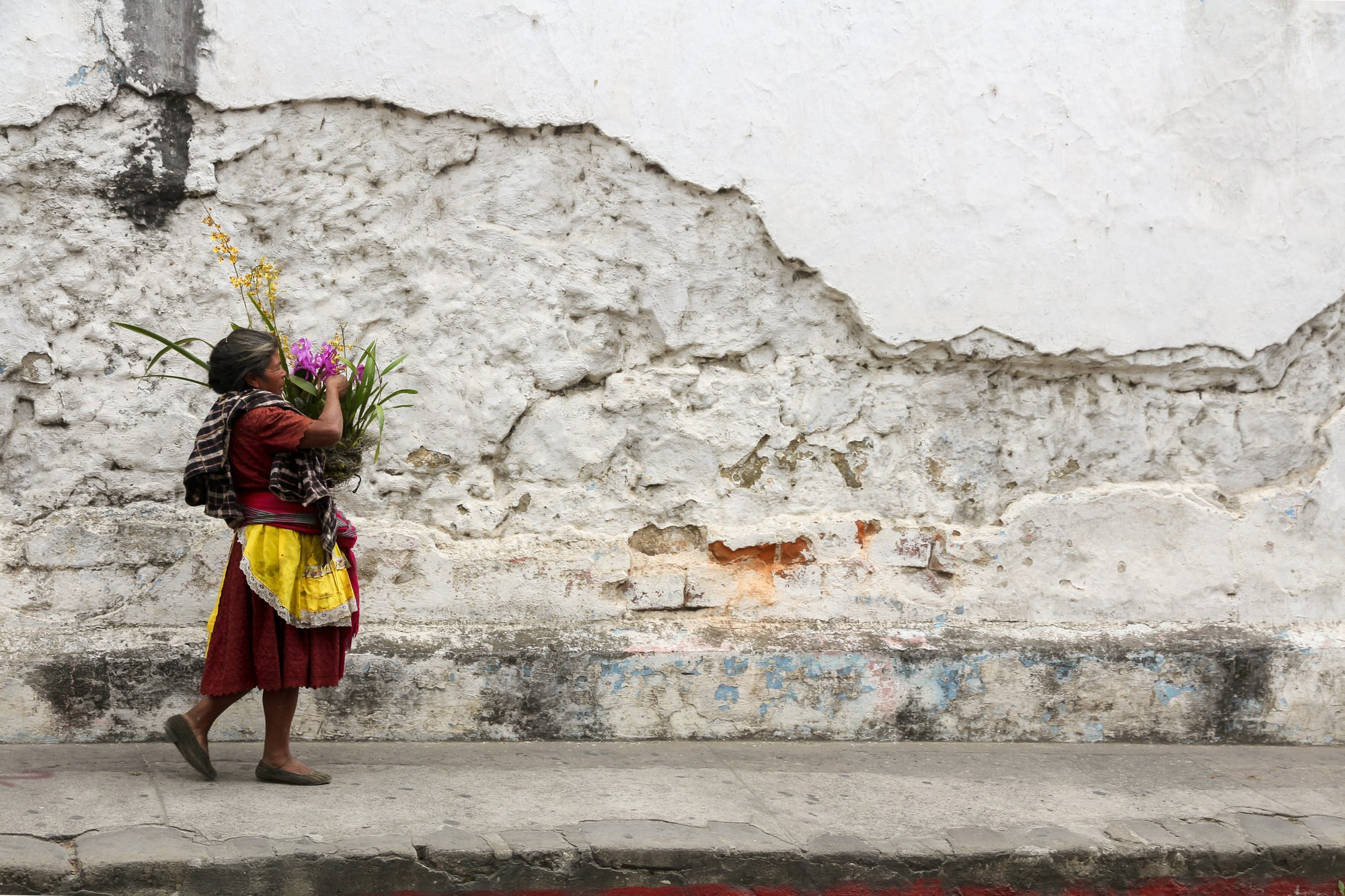 A woman carries a basket of flowers next to the cobblestone streets and crumbling walls of Antigua, Guatemala.
