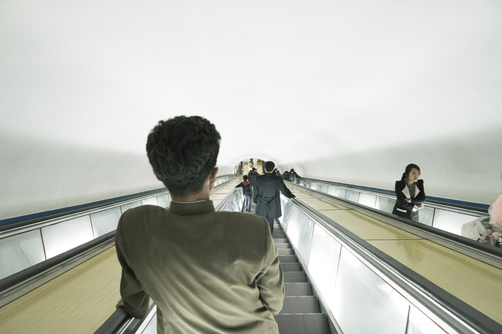 man riding escalator
