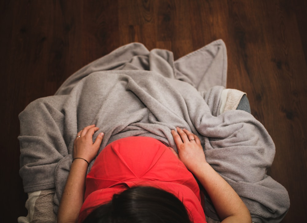 woman covering herself in gray blanket