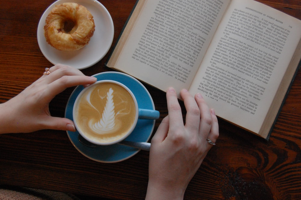 person holding blue ceramic teacup beside the book