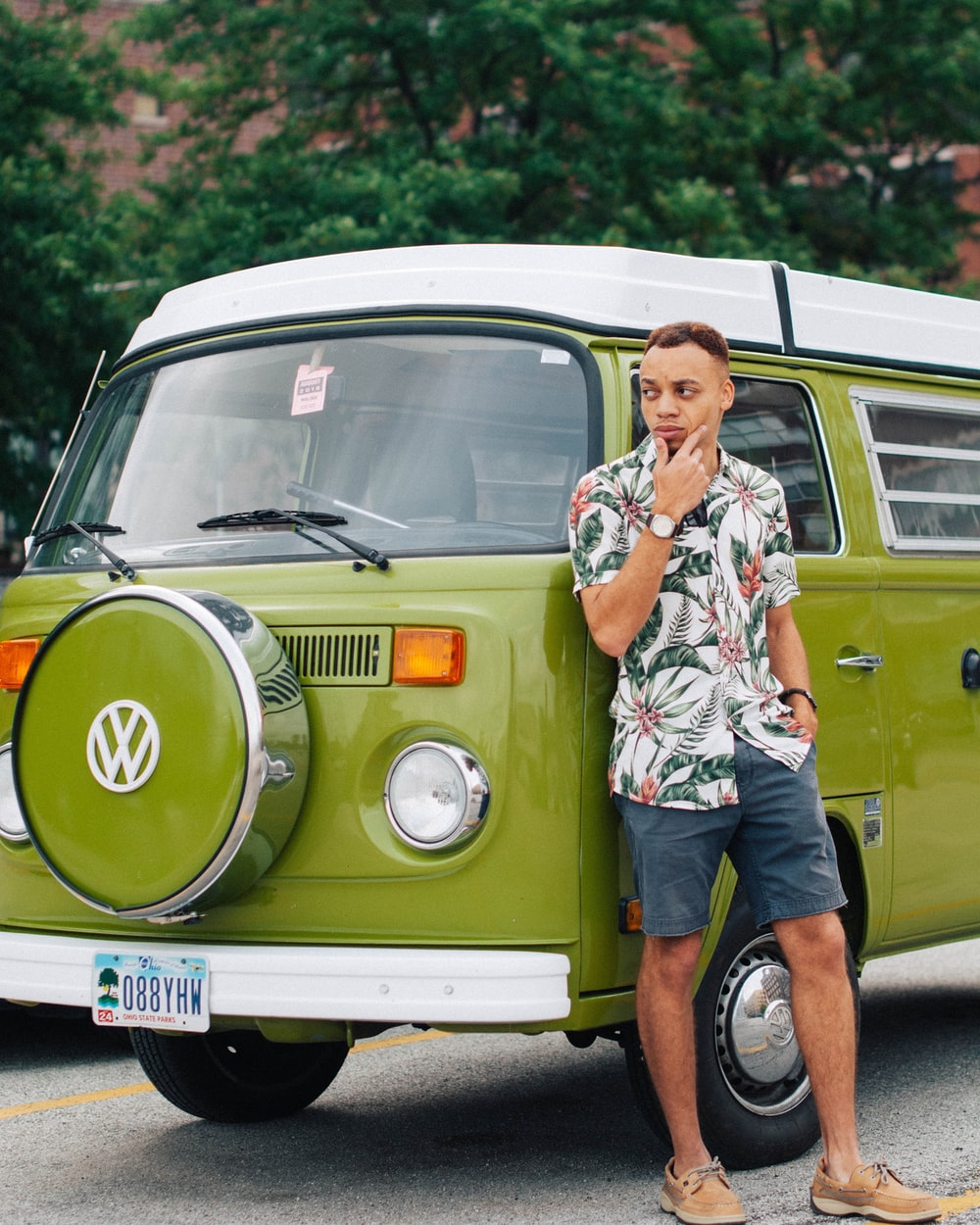 man leaning on green Volkswagen vehicle