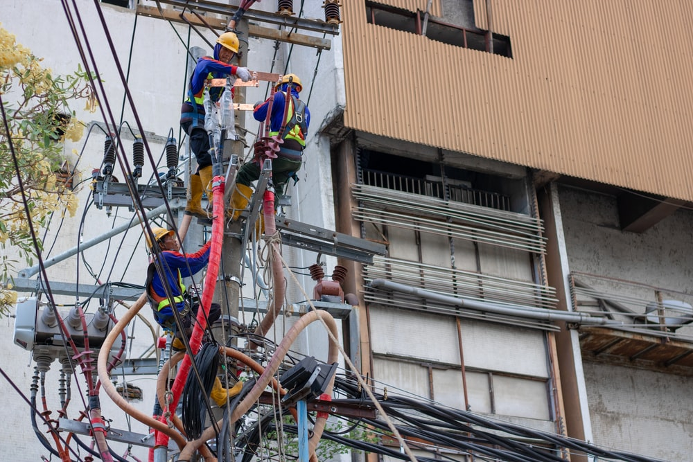 group of people fixing the wires on post