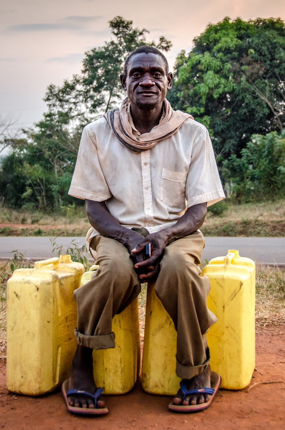 man sitting on yellow plastic containers