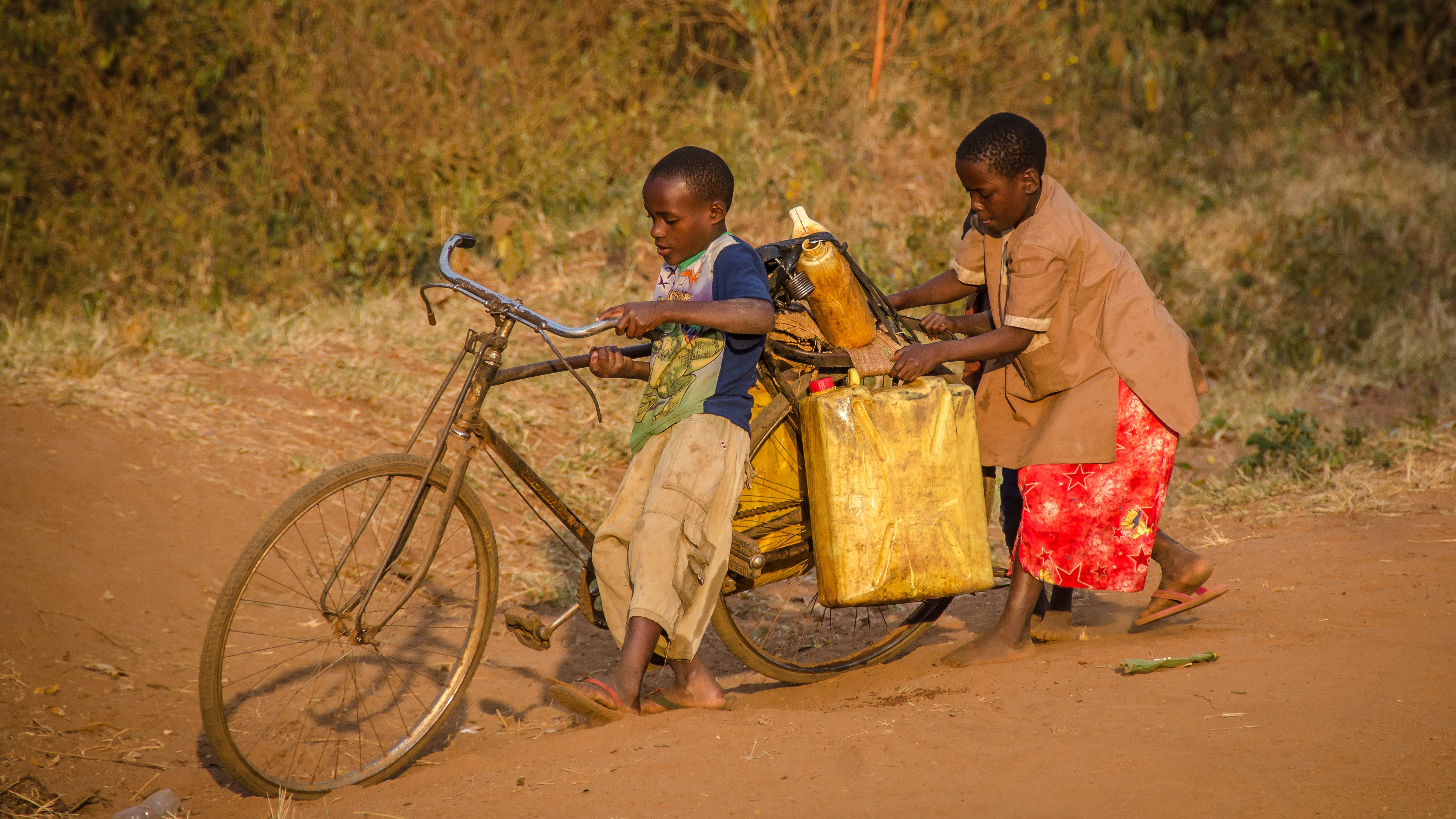 two kids using brown bike with cargo