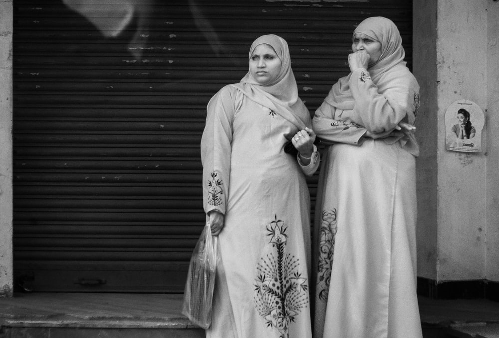 grayscale photography of two women standing near roll-up door