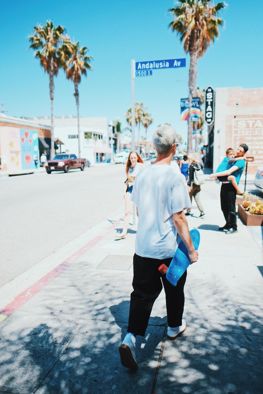 man walking while holding blue longboard