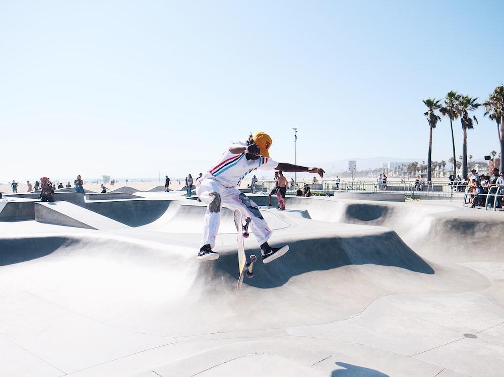 man jumping wearing white track pants and jacket during daytime