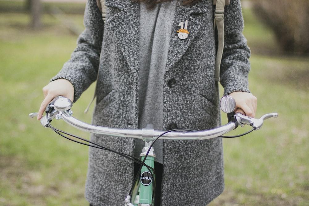 woman gray coat riding bike