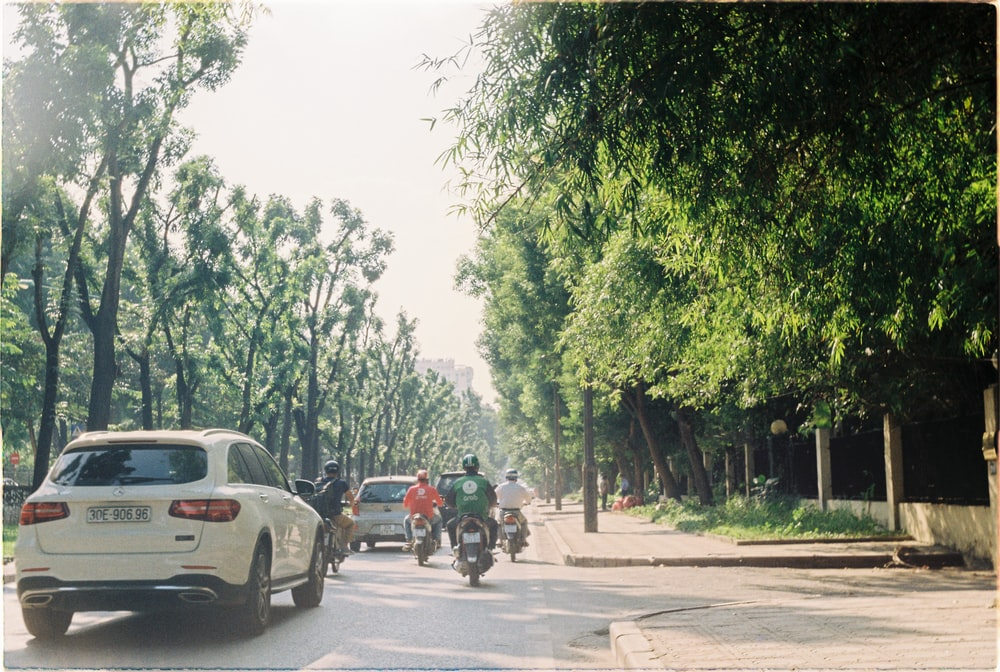 white SUV and black motorcycle at road beside green trees