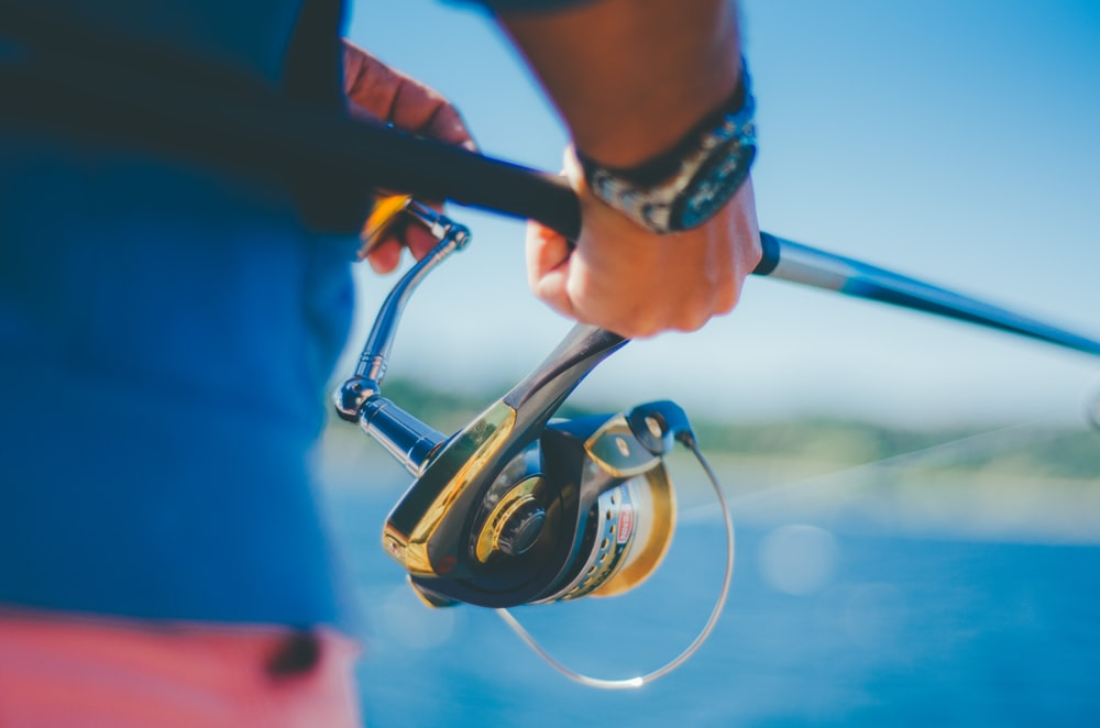 person holding black fishing rod with fishing reel