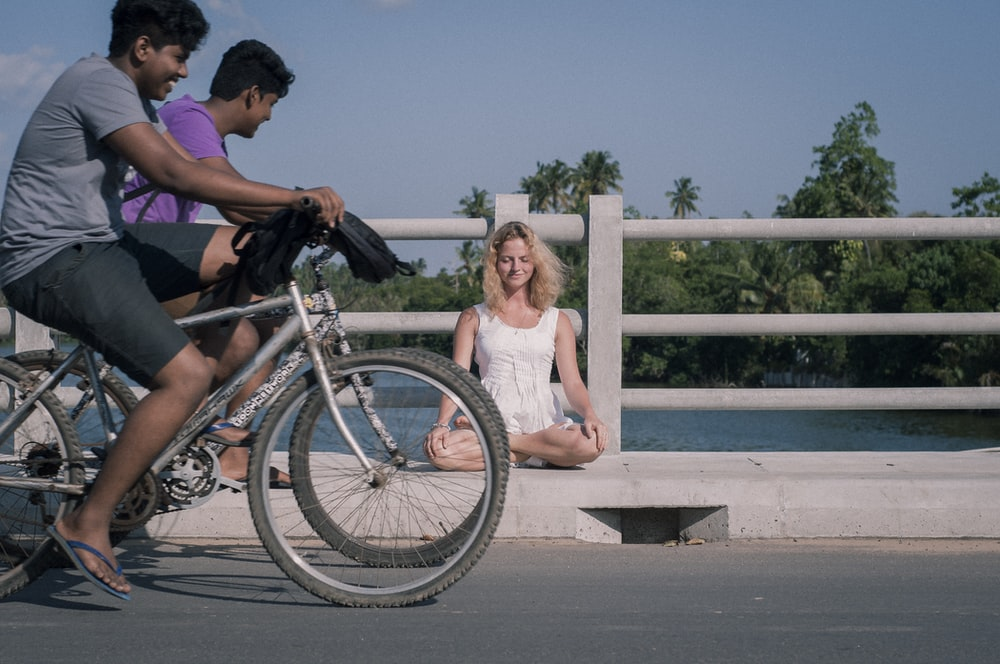 woman sits on curb with two men on bikes passing