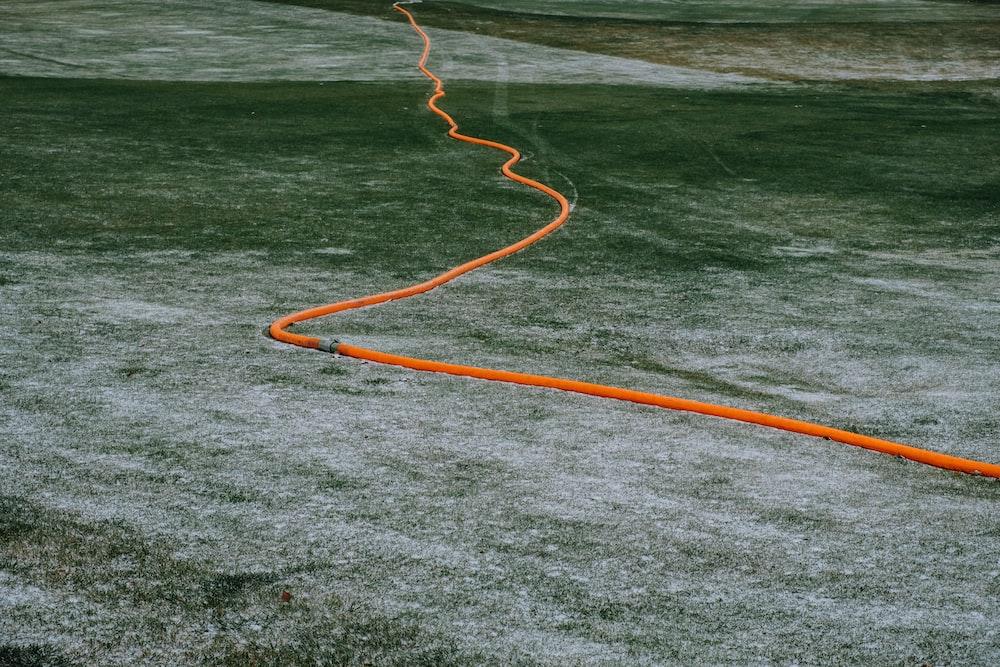 orange hose on body of water