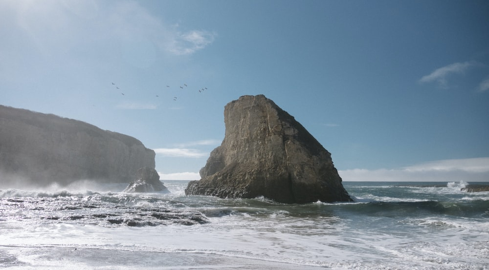seagulls flying in formation over brown butte in beach