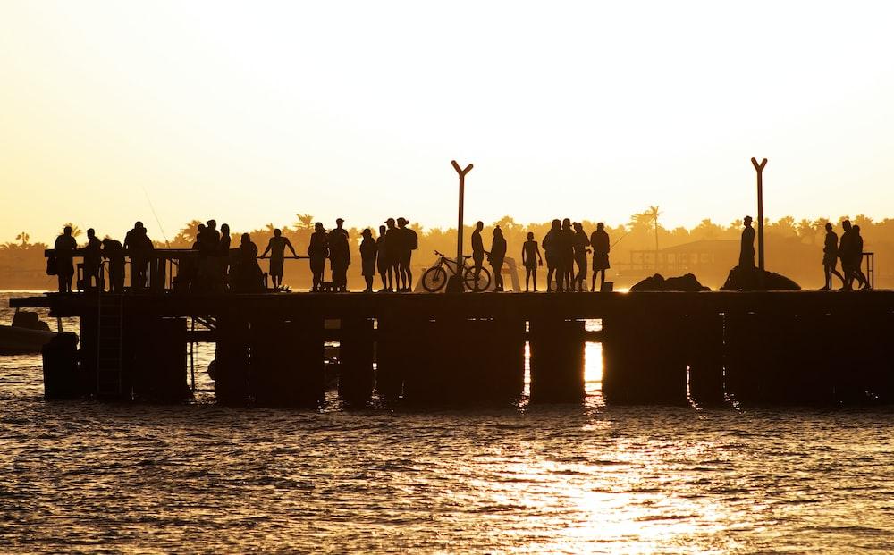 people standing and walking on beach dock near calm sea