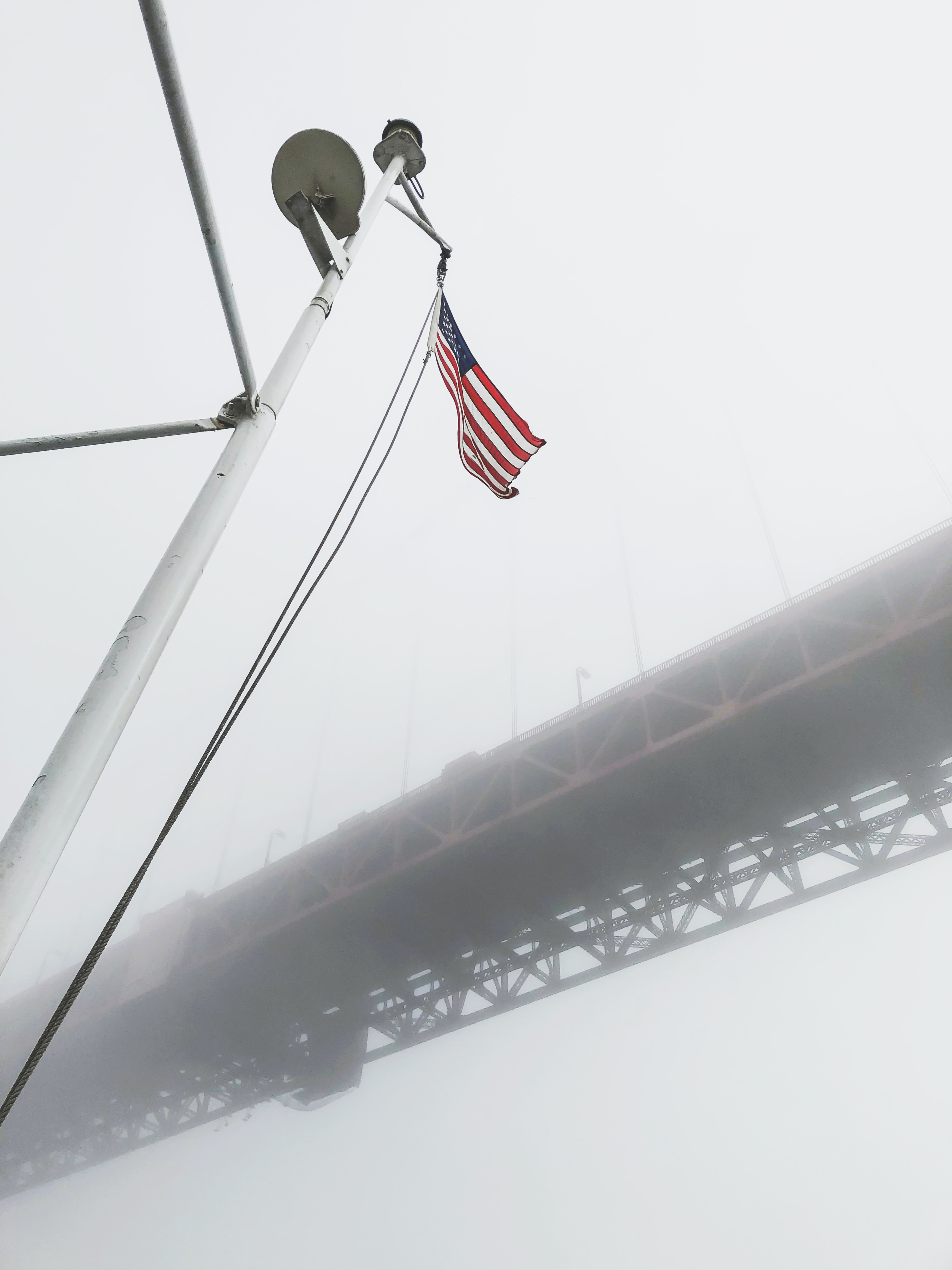 low angel photography of waving USA flag under red bridge