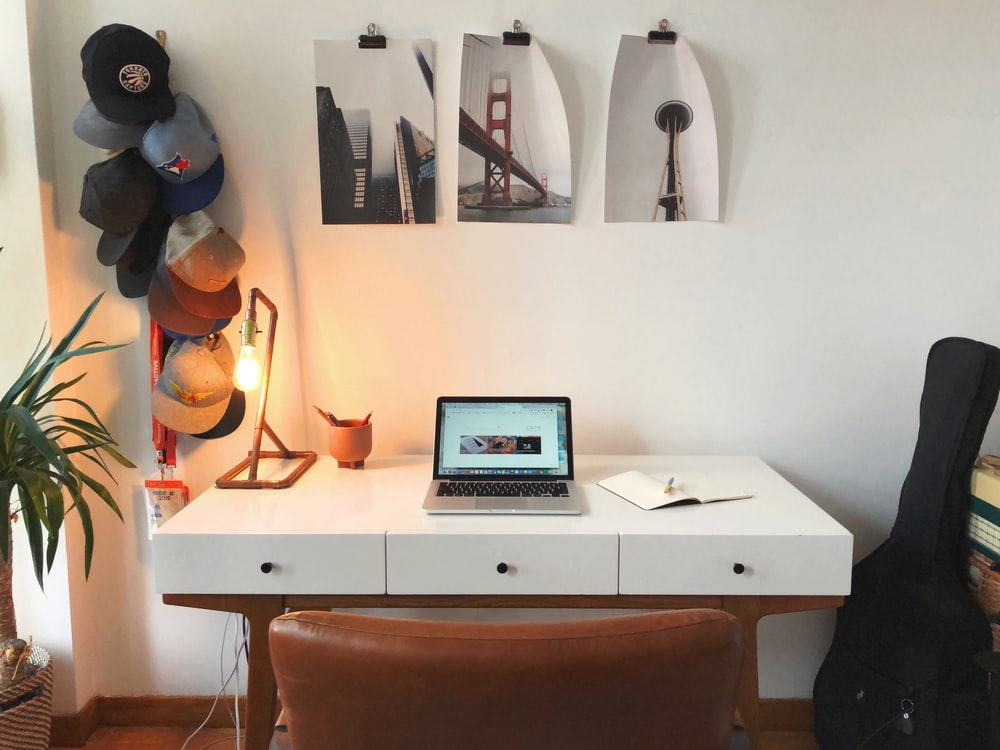 open laptop on table beside guitar bag and hanging hats