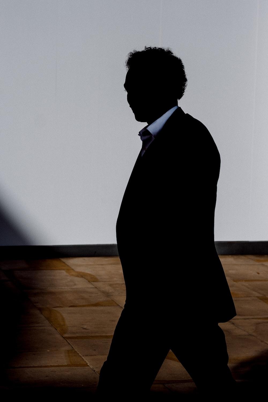 silhouette of man walking inside room