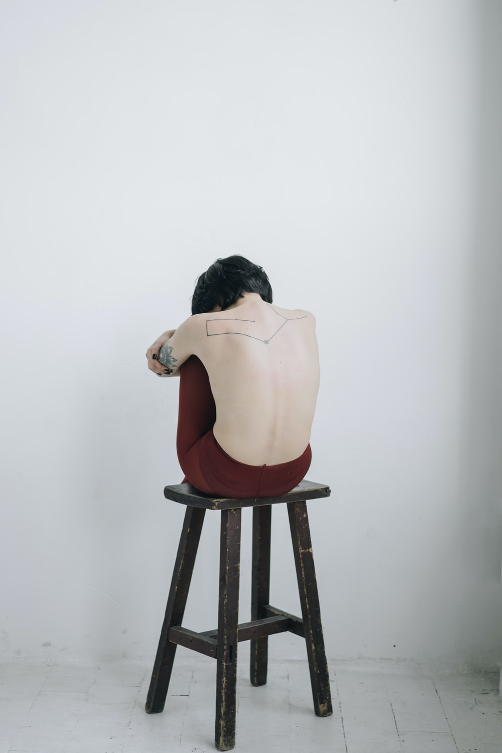 topless woman sitting on chair near white wall