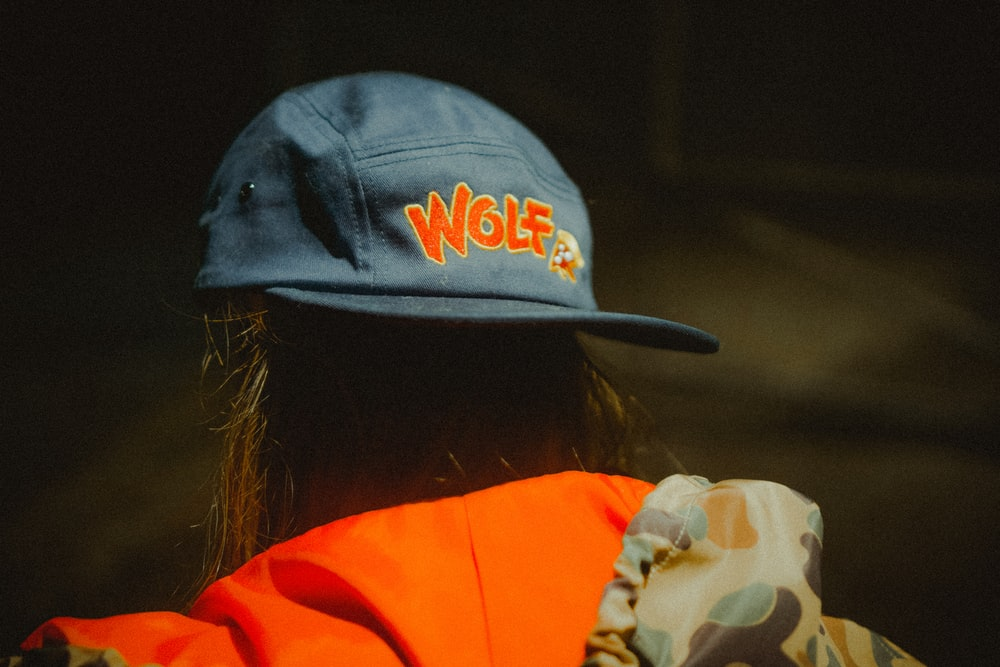 woman wearing blue Wolf fitted cap