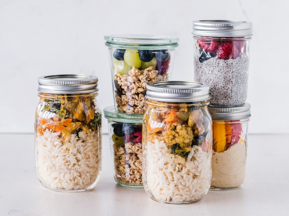 six full clear glass jars on white surface