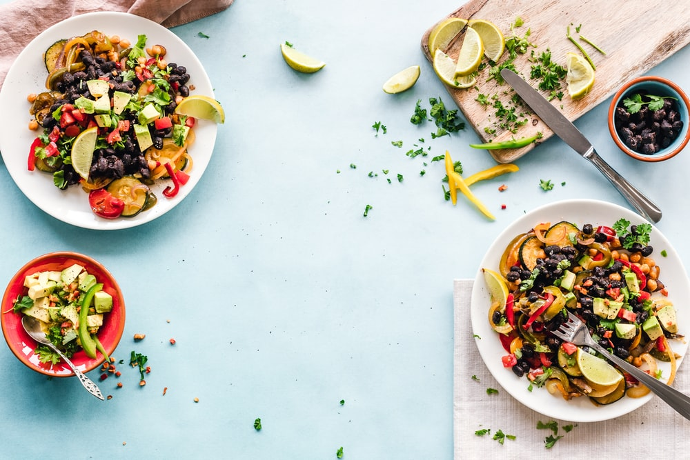 three bowls of salad dish with lemon on table