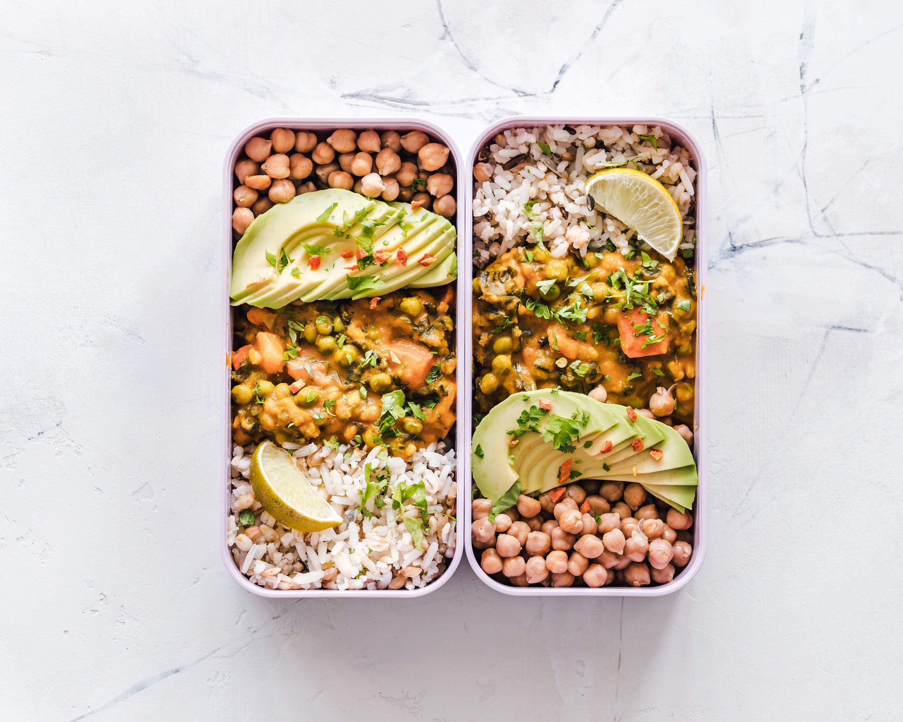 Meal Prep Lunch Box mit Kichererbsen, Curry, Reis und Avocado