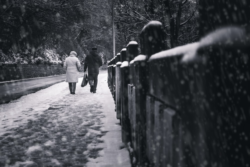 two people walking on sidewalk at the snow