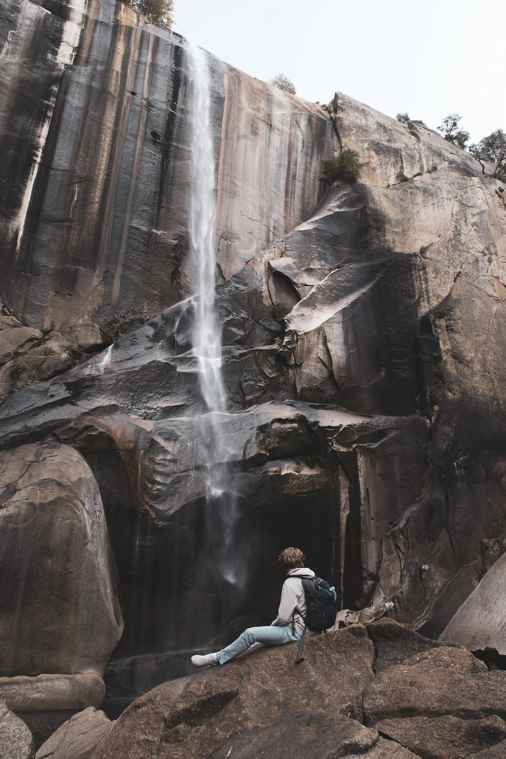 person sitting on rock in front of waterfall