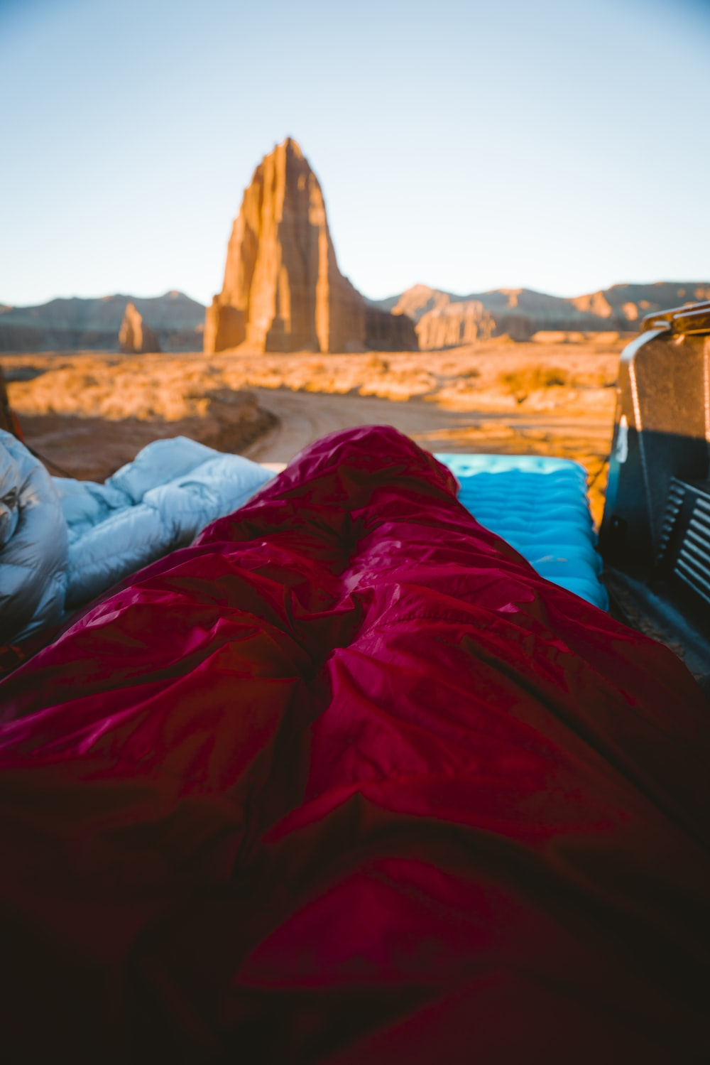 person in sleeping bag overlooking rock formations