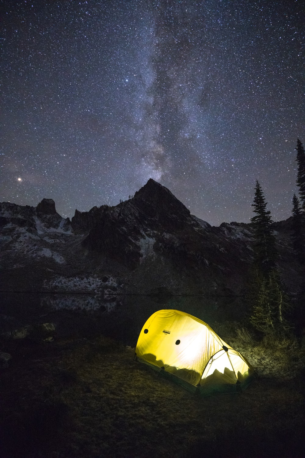 lighted lamp in yellow dome tent under milky way